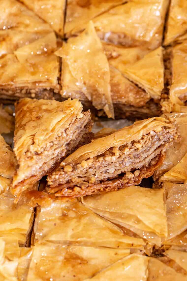 Sliced baklava pieces laid out in a baking sheet.