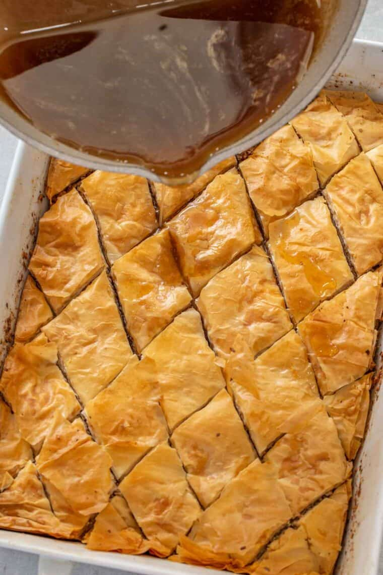 Cooked baklava in a white casserole dish with the sweet syrup being poured over the baklava.