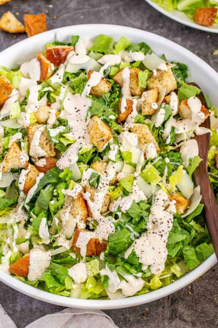 Caesar salad in a white bowl topped with Caesar salad and ground black pepper.