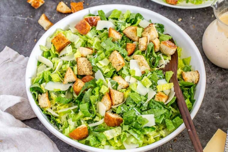 A large white bowl loaded with romaine, croutons, and fresh grated parmesan cheese with a wooden spoon.