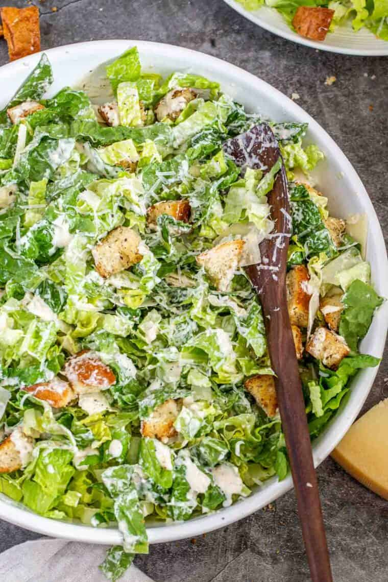 Caesar salad tossed in the caesar salad dressing in a white bowl with a wooden spoon.