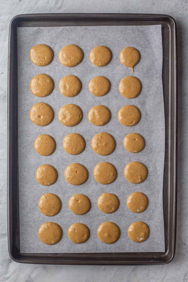 Piped out coffee macarons on a baking sheet ready to be baked.