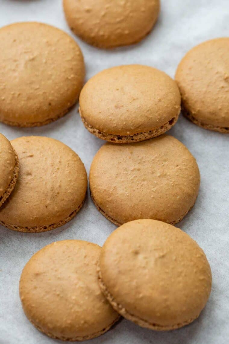 Coffee macarons shells on a baking sheet laid out.