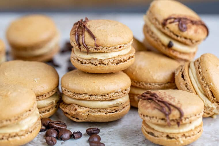Coffee macarons stacked on top of each other next to coffee beans.