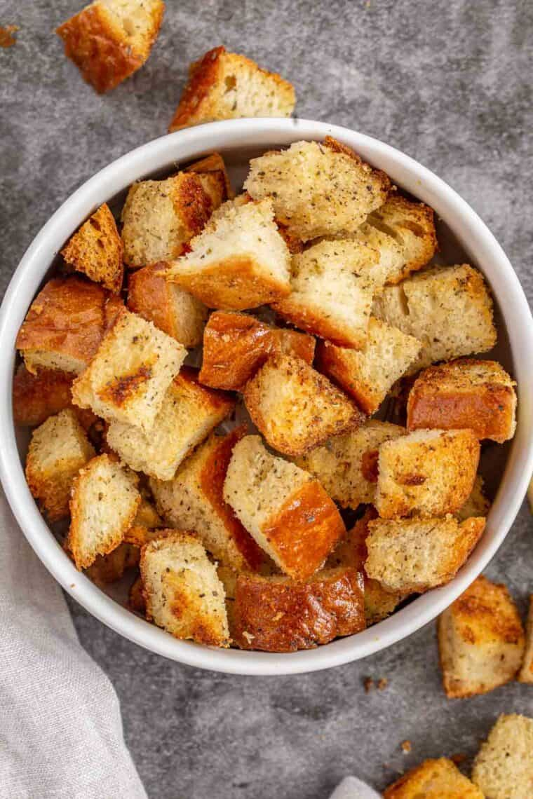 Homemade croutons in a white bowl with croutons next to the bowl.