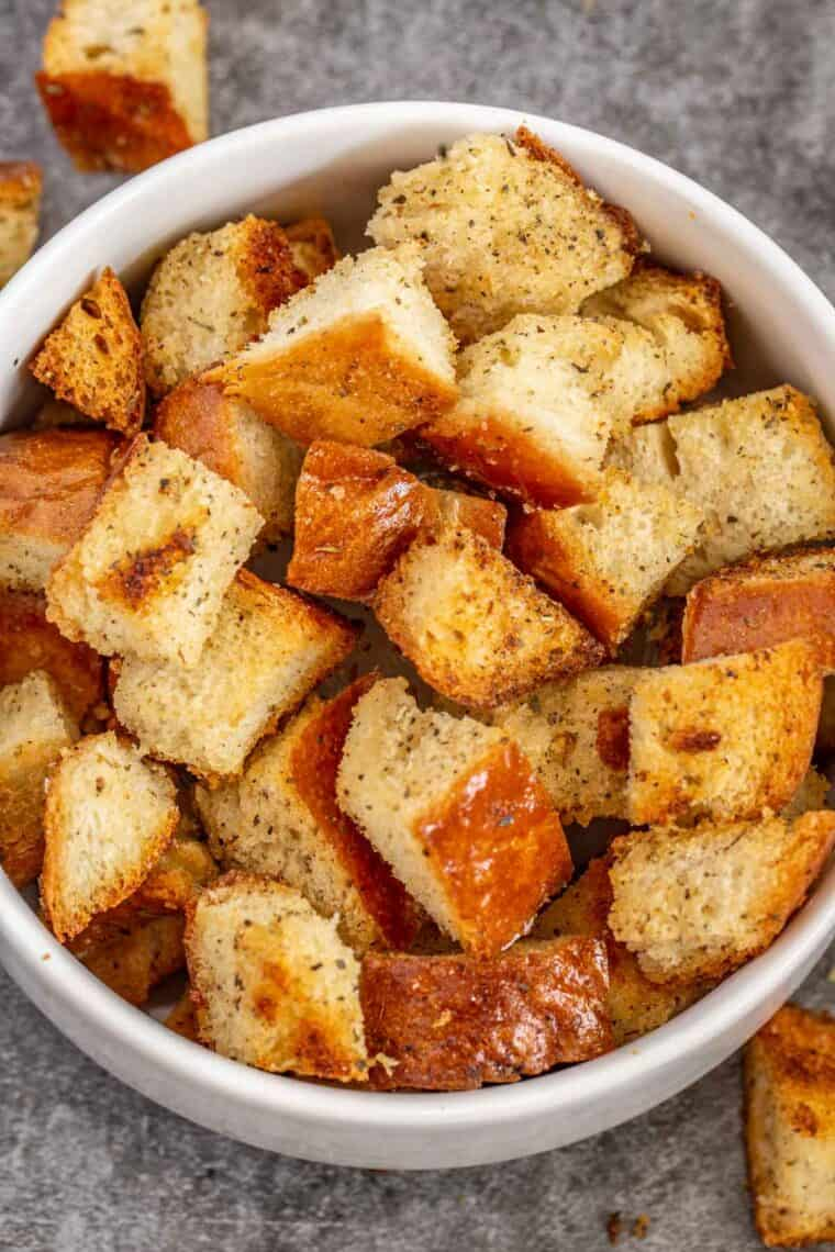 Crispy homemade croutons in a white bowl.