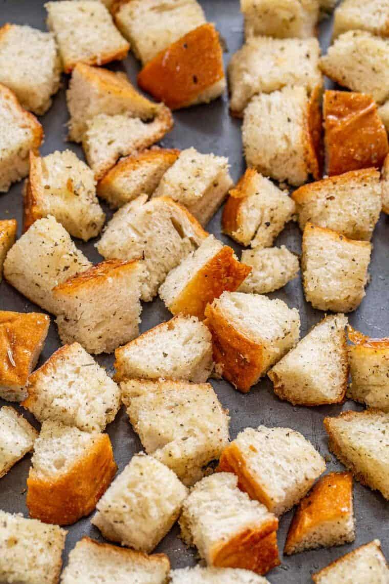 Uncooked seasoned croutons on a baking sheet.