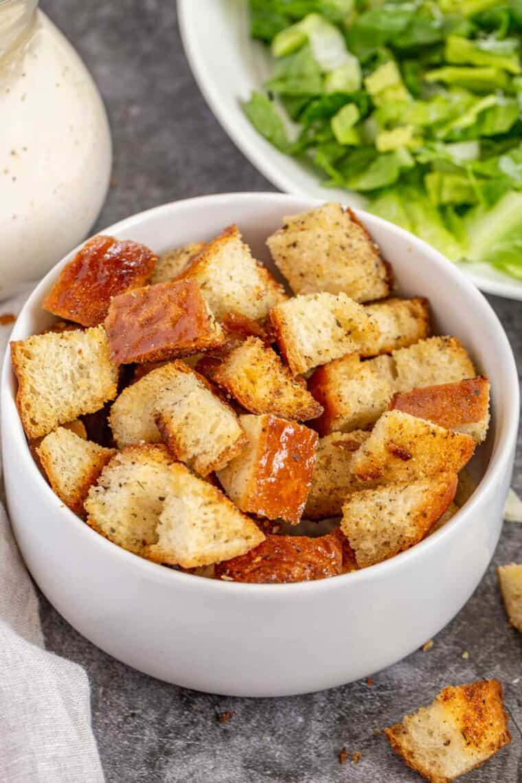 White bowl full of homemade croutons next to a rag and crouton crumbs.