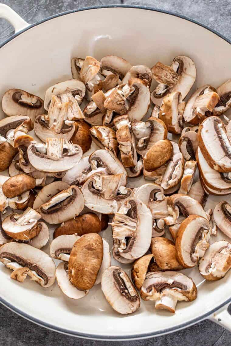 Sliced mushrooms in a white skillet uncooked.