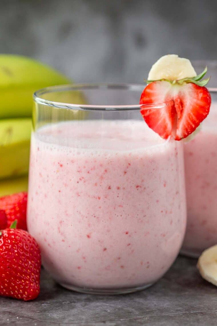A cup filled with strawberry banana smoothie with a strawberry and banana on the rim of the cup.