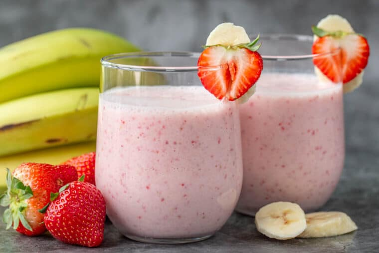 Two glass cups full of creamy strawberry and banana smoothies next to fruit.