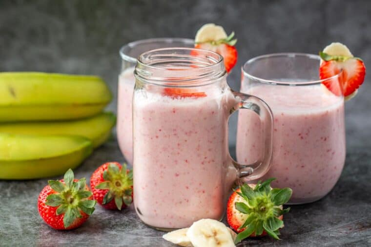 Three cups of strawberry smoothies next to a stack of bananas, strawberries and sliced bananas.