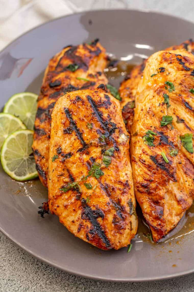 Tender cilantro lime chicken on a gray plate topped with fresh chopped greens.