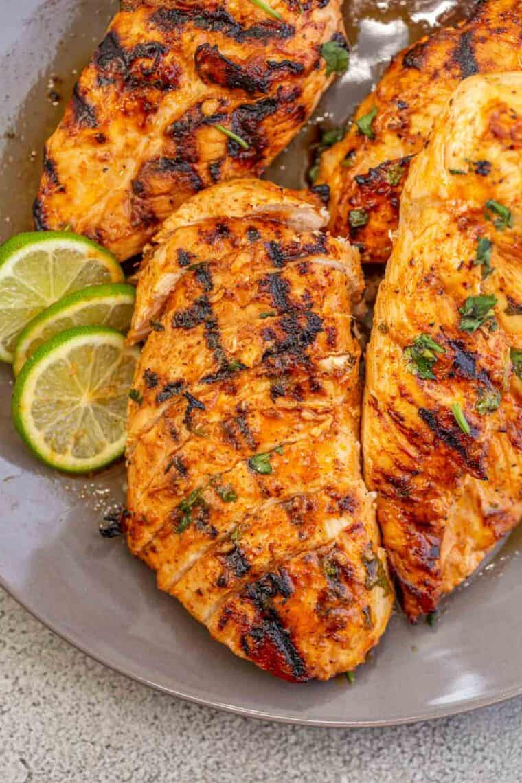 Cilantro lime chicken on a gray plate topped with chopped cilantro and lime slices.