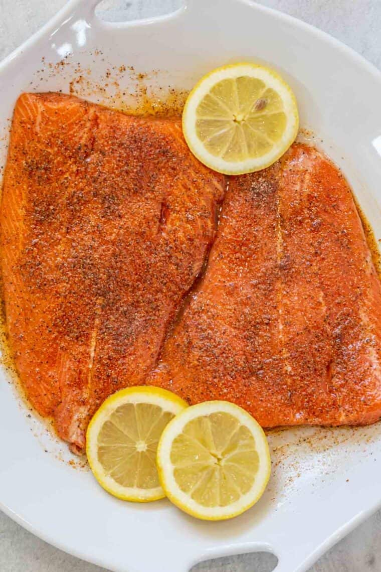 White bowl of salmon fillets marinating in the grilled salmon marinade.