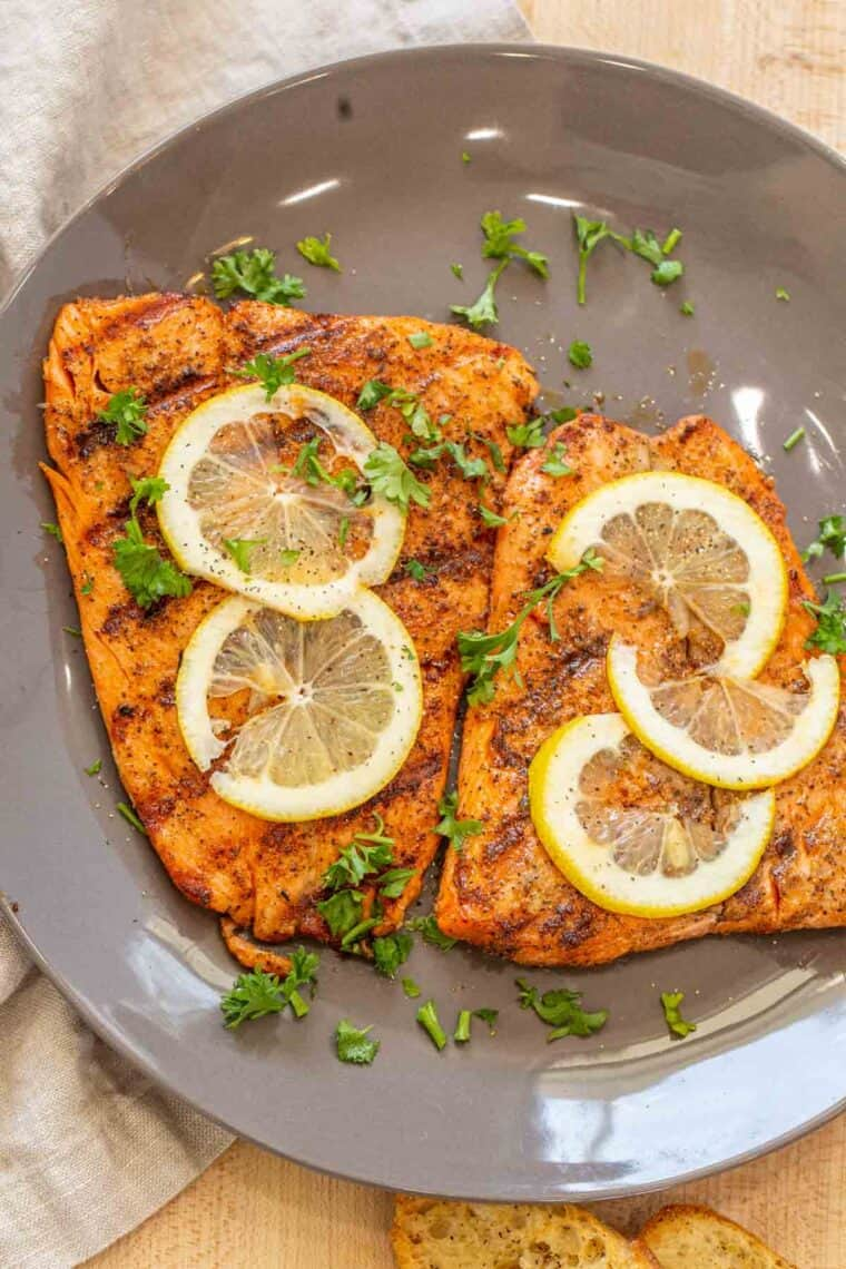 Two grilled salmon fillets on a gray plate topped with lemon slices and fresh chopped greens.