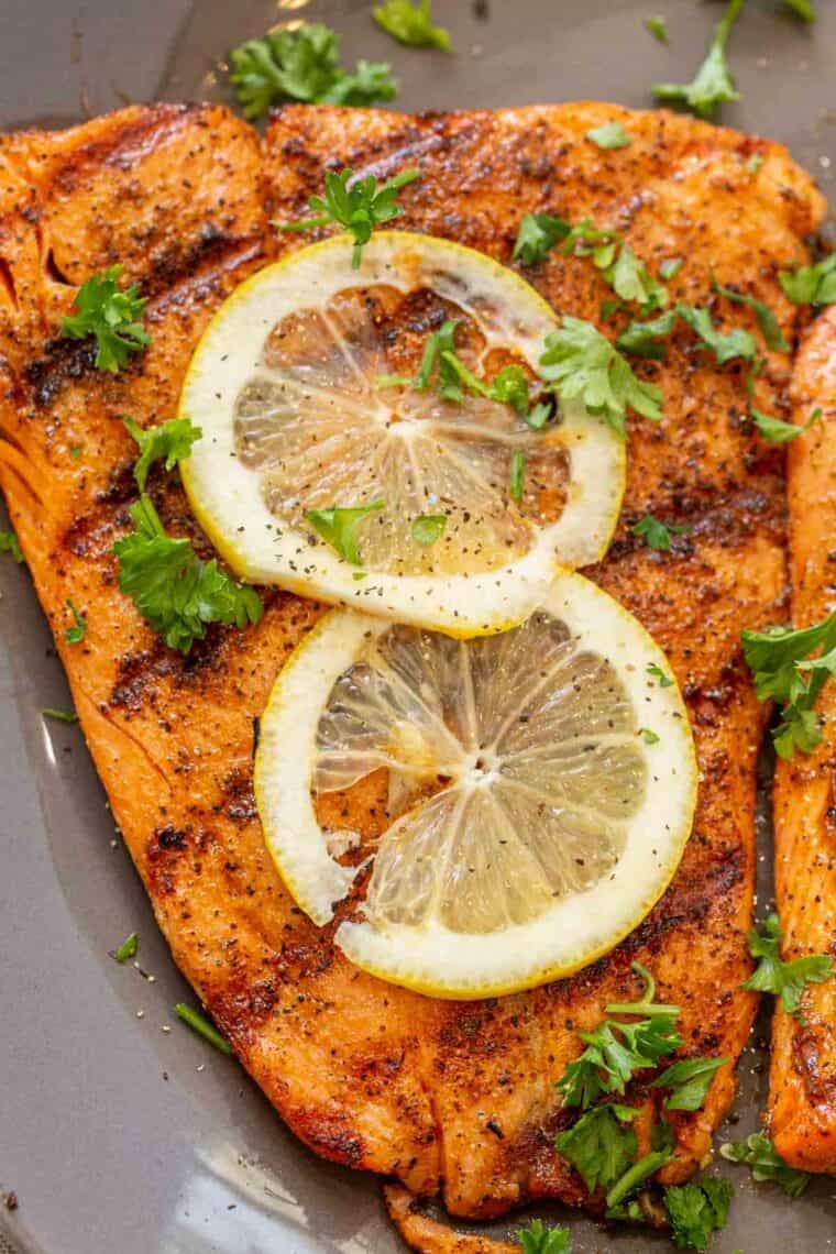 Grilled salmon fillet topped with fresh chopped greens and lemon slices.