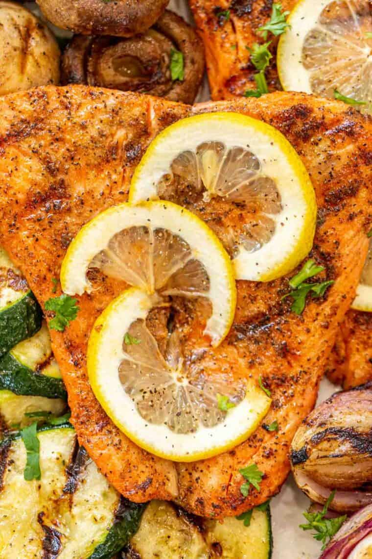 Salmon fillets topped with lemon slices and fresh chopped greens next to grilled vegetables.