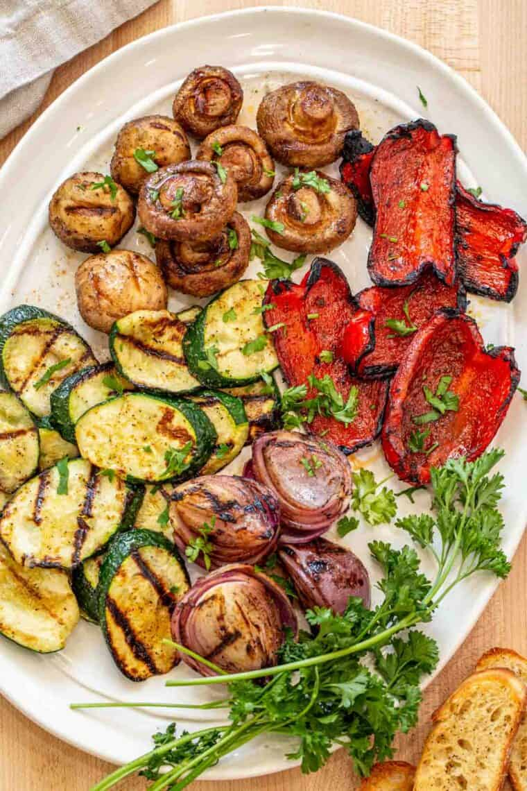 Grilled vegetables laid out on a white platter topped with fresh chopped cilantro.