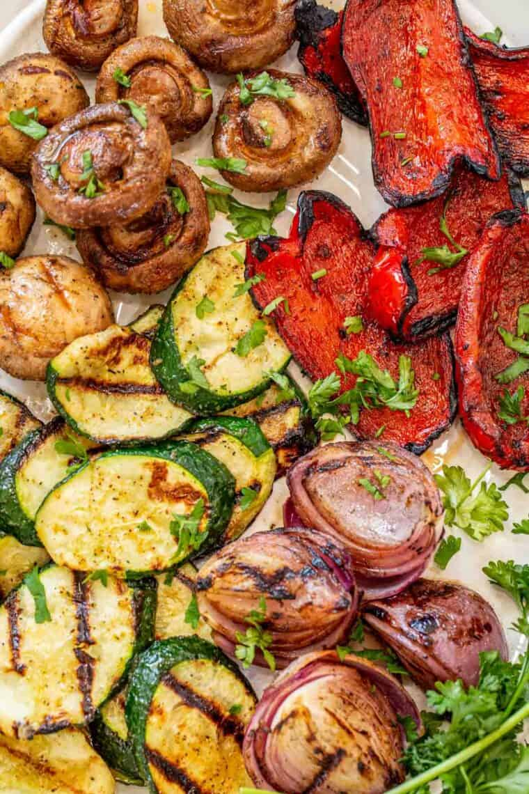 Grilled veggies on a white plate topped with fresh greens and black pepper.