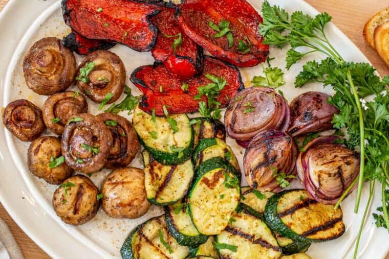 A white platter loaded with grilled red pepper, zucchini, mushrooms, and red onion topped with greens.