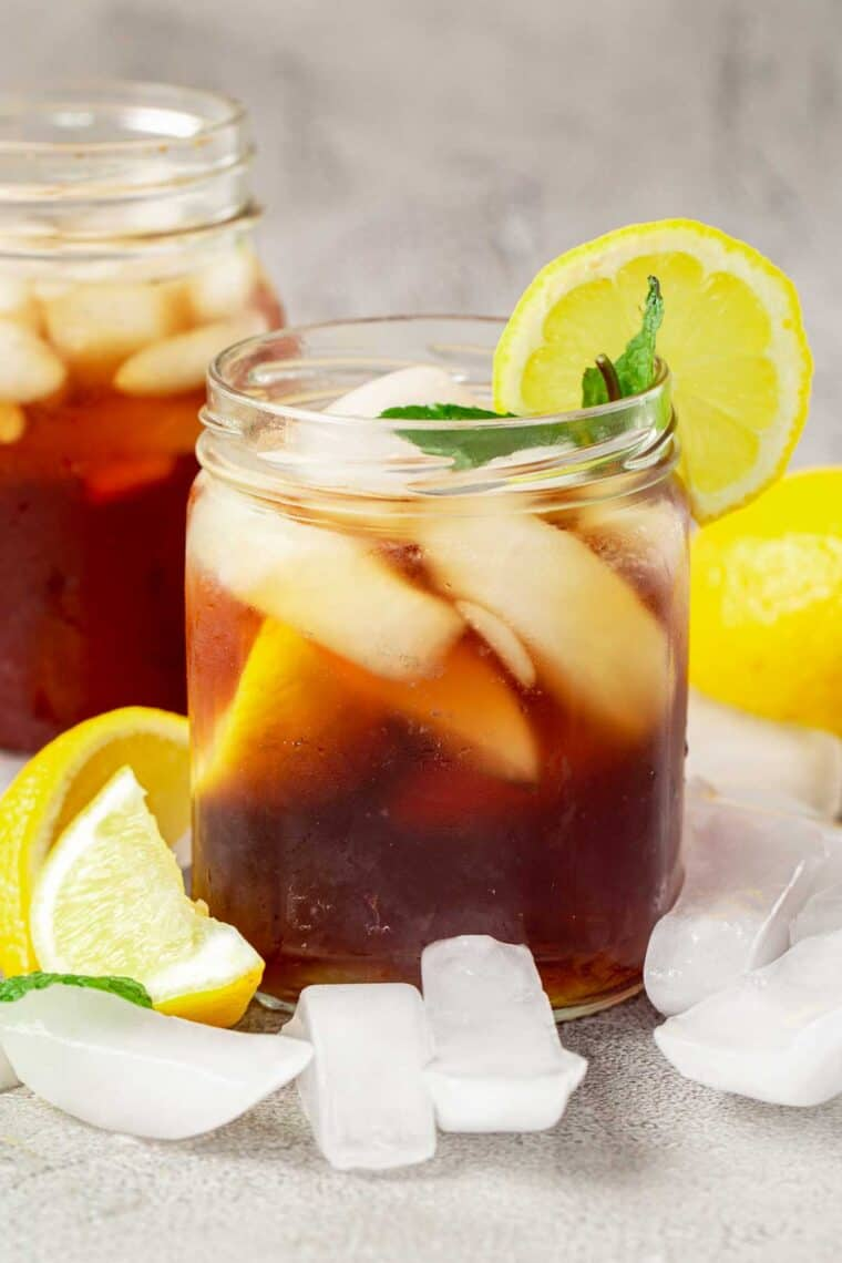 Homemade sweet tea in mason jars with lemon slices and mint leaves.