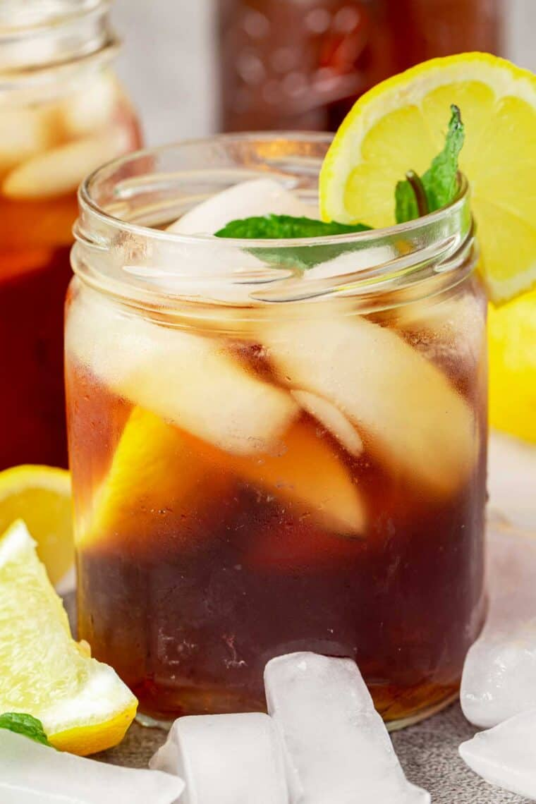 A mason jar loaded with ice, lemon slices and mint leaves next to lemon slices and cubed ice.