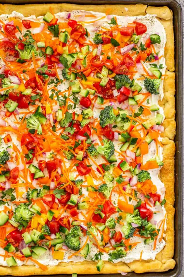 Cold veggie pizza in a baking sheet topped with fresh greens.