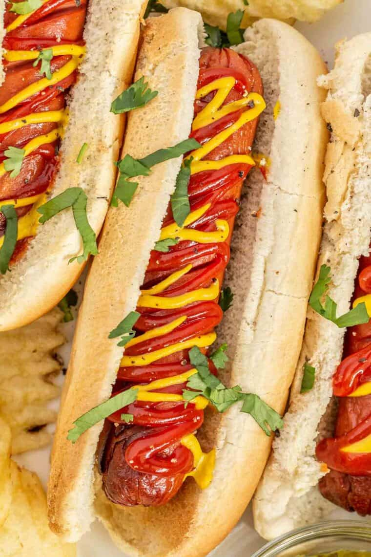 Juicy hot dogs in a bun topped with ketchup and mustard and fresh chopped greens.