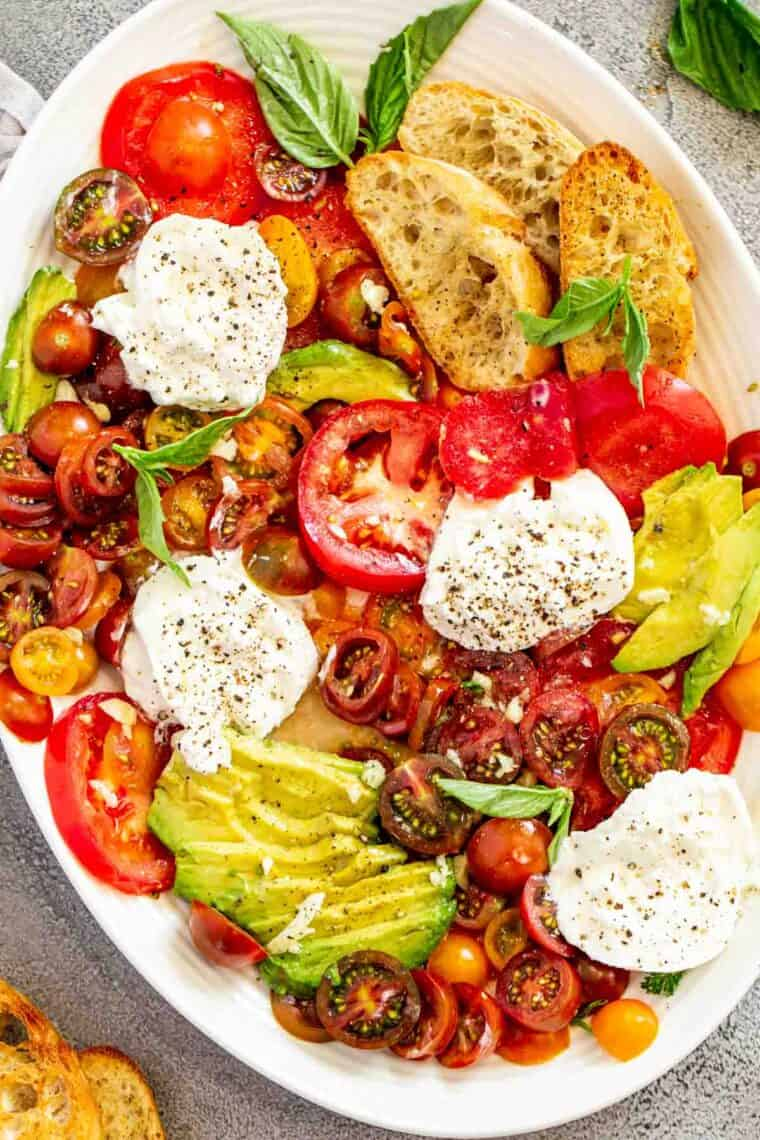 Burrata salad in a white serving platter topped with fresh basil and fresh black pepper.