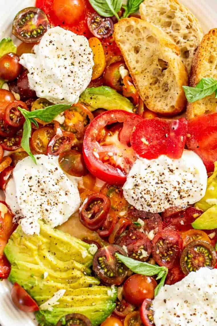 Burrata, tomatoes, basil and crostini on a white platter topped with fresh black pepper.