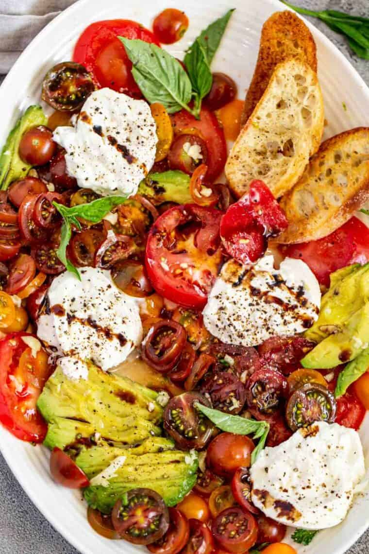 Simple burrata salad recipe in a white serving bowl topped with glaze.