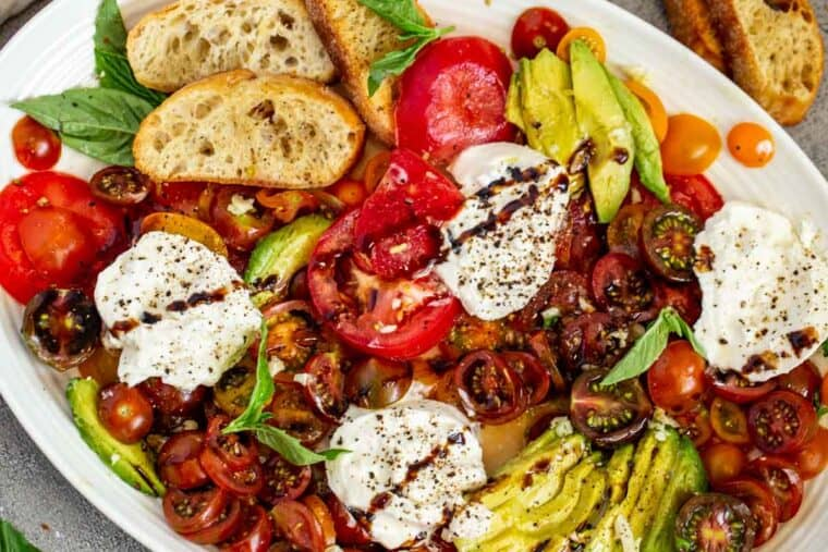 Light burrata salad recipe on a white platter topped with balsamic glaze.