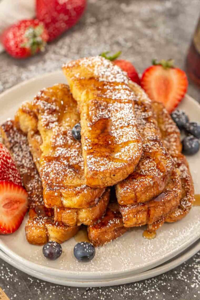 French toast sticks on a plate topped with powdered sugar and maple syrup.