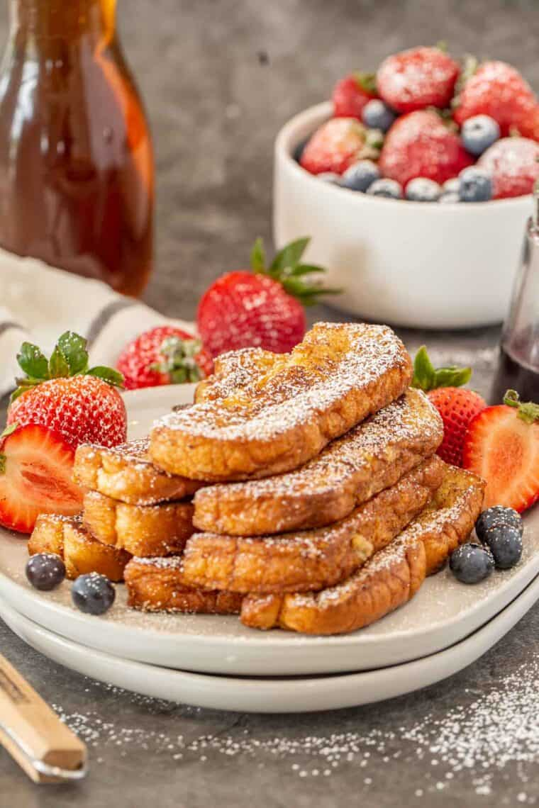 French toast cinnamon sticks on a plate topped with powdered sugar and berries.