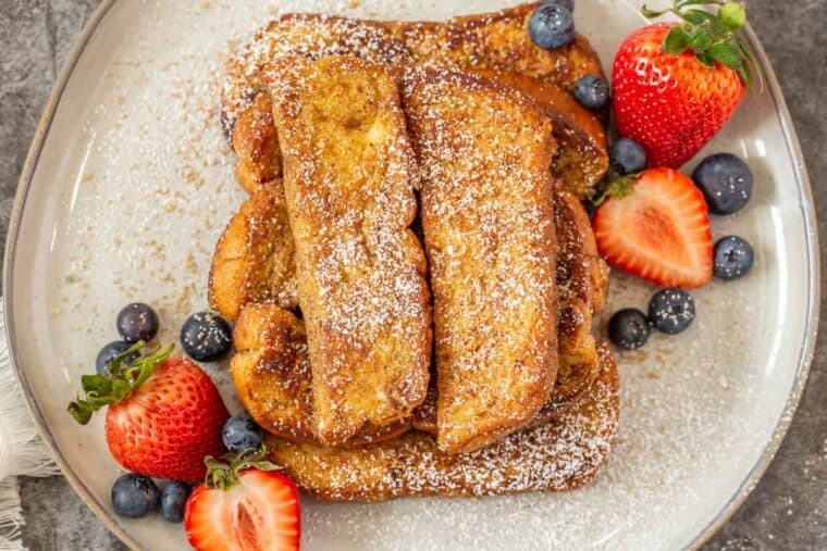 Homemade cinnamon French toast sticks topped with powdered sugar and berries.