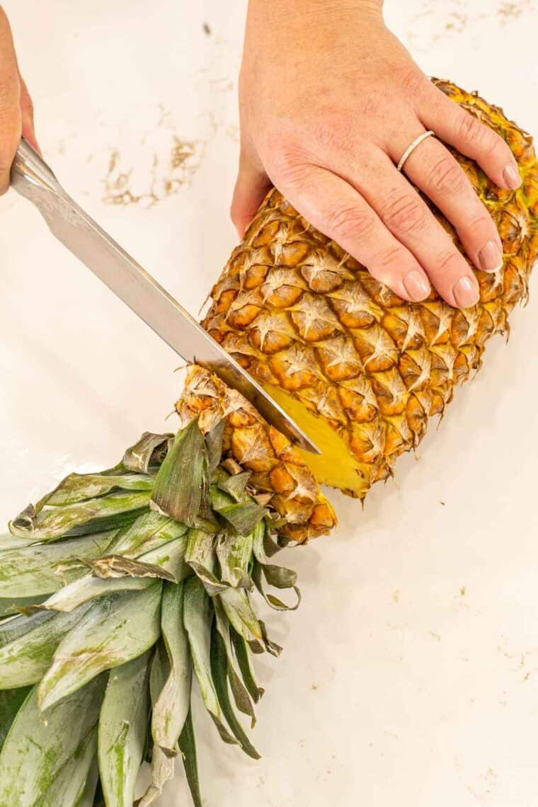 Pineapple being cut with a knife on a cutting board.