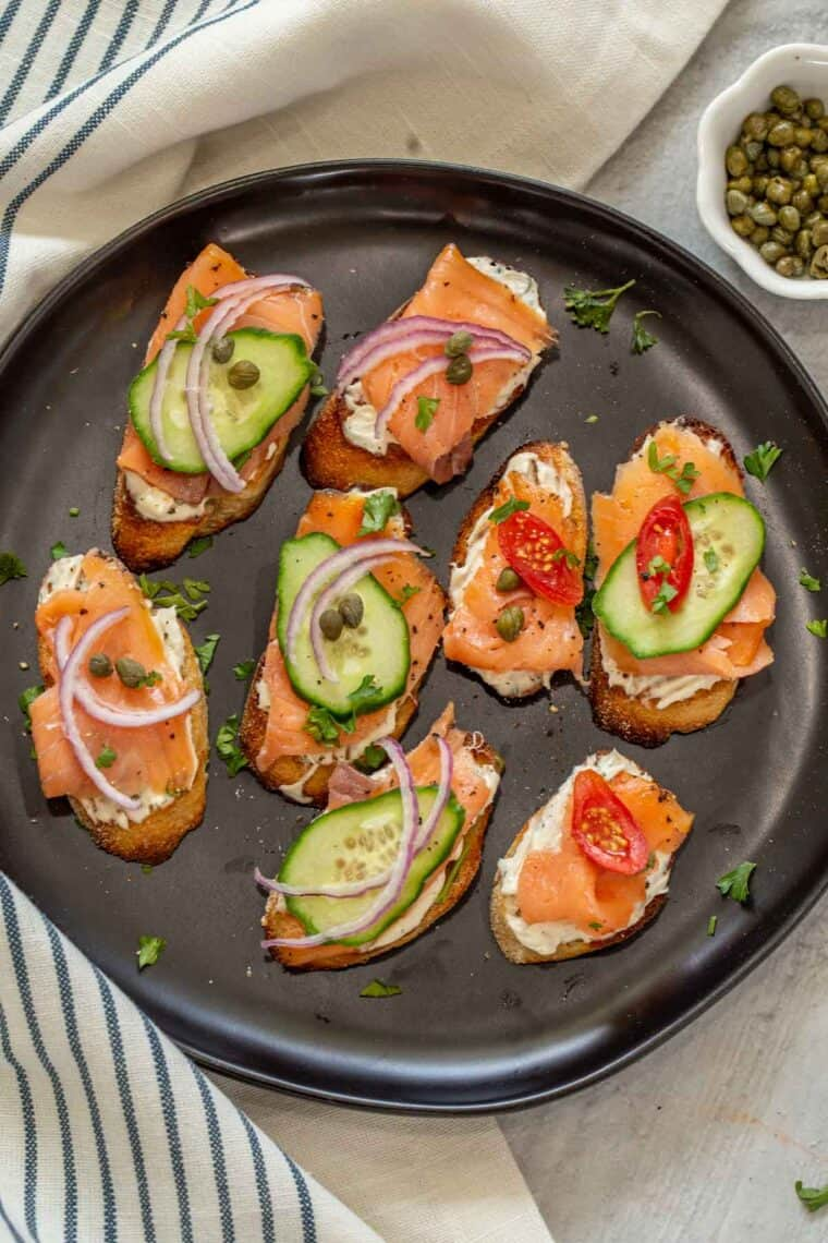 Smoked salmon appetizer crostini on a black plate topped with fresh greens.
