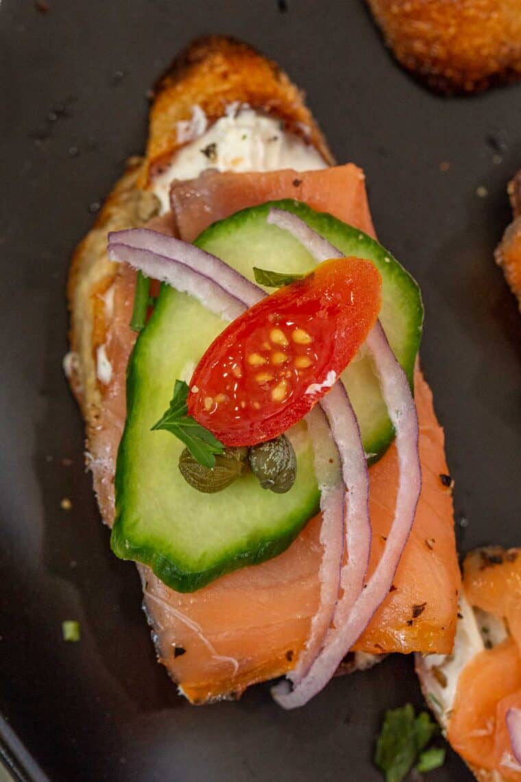 Smoked salmon crostini topped with cucumber, red onion, and tomato slices.
