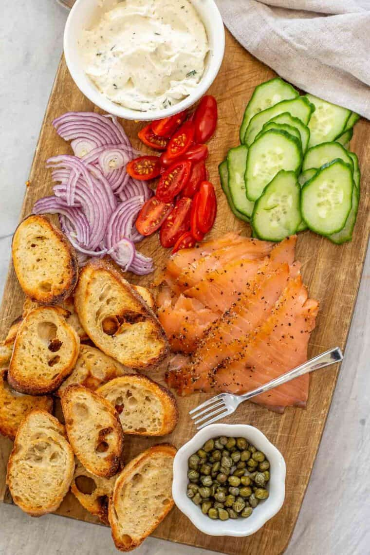 All the ingredients needed for this smoked salmon appetizer recipe on a cutting board.