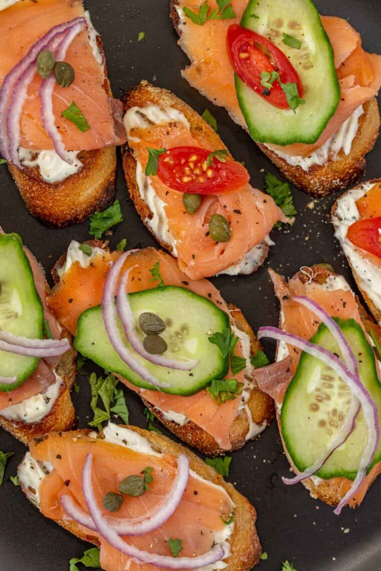 Smoked salmon crostini on a black plate topped with toppings of your choice and fresh chopped greens.