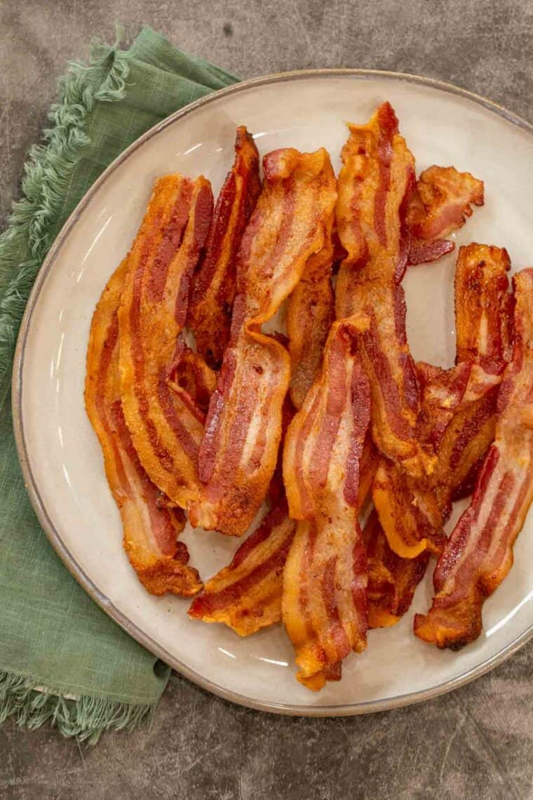 Air fryer bacon strips on a plate next to a green rag.