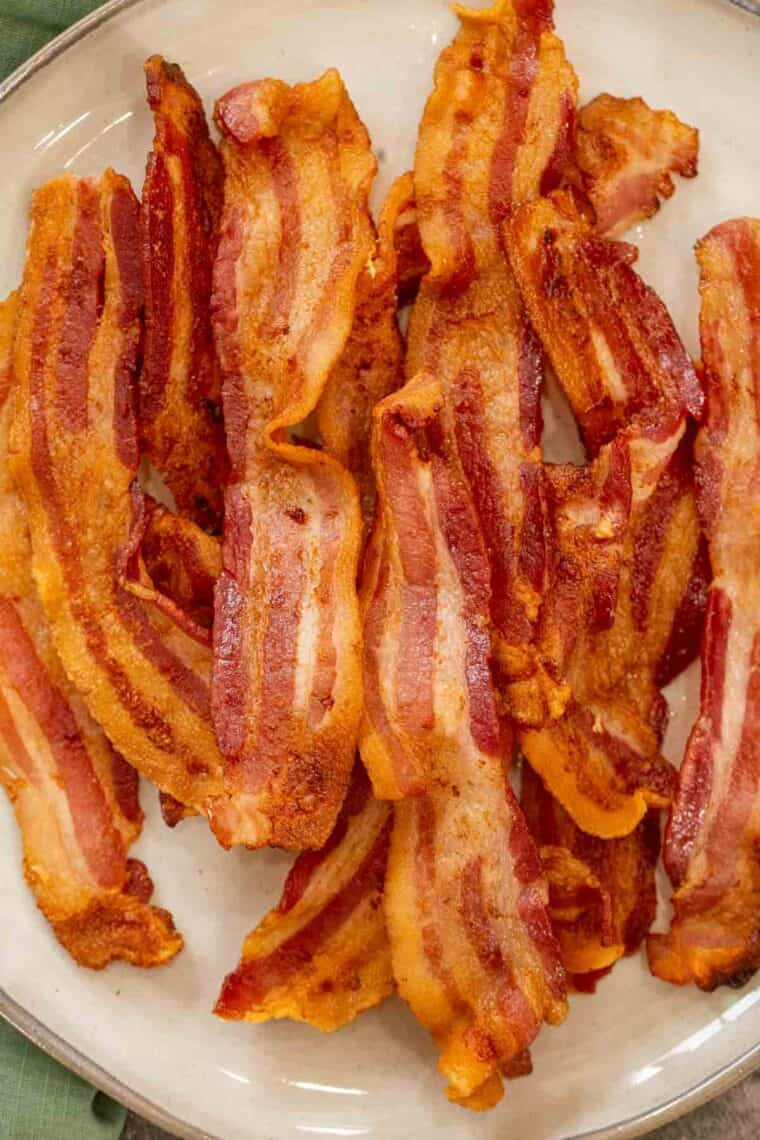 Crispy bacon strips stacked on top of each other on a tan plate.