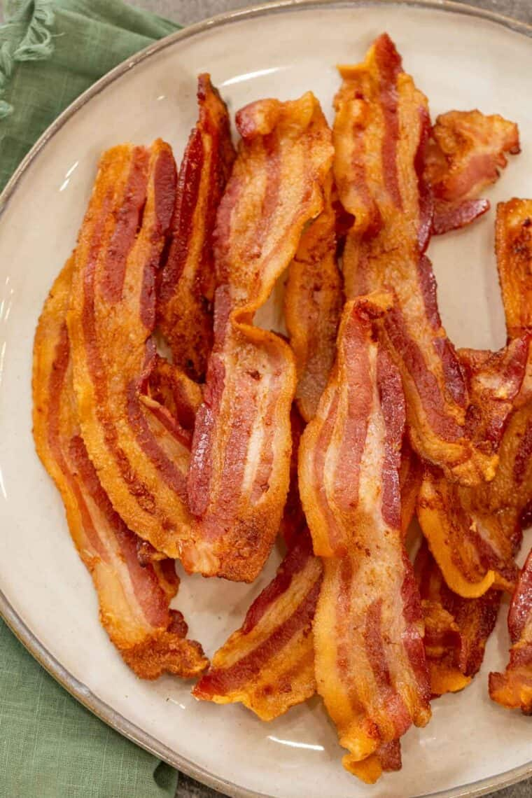 A tan plate loaded with crispy bacon strips next to a green rag.