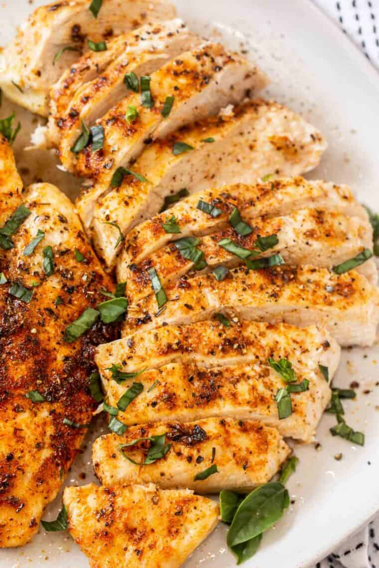 Sliced chicken breast on a white plate topped with fresh greens.