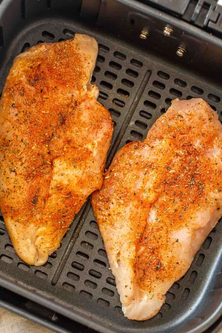 Seasoned chicken breast in the air fryer basket ready to be cooked.