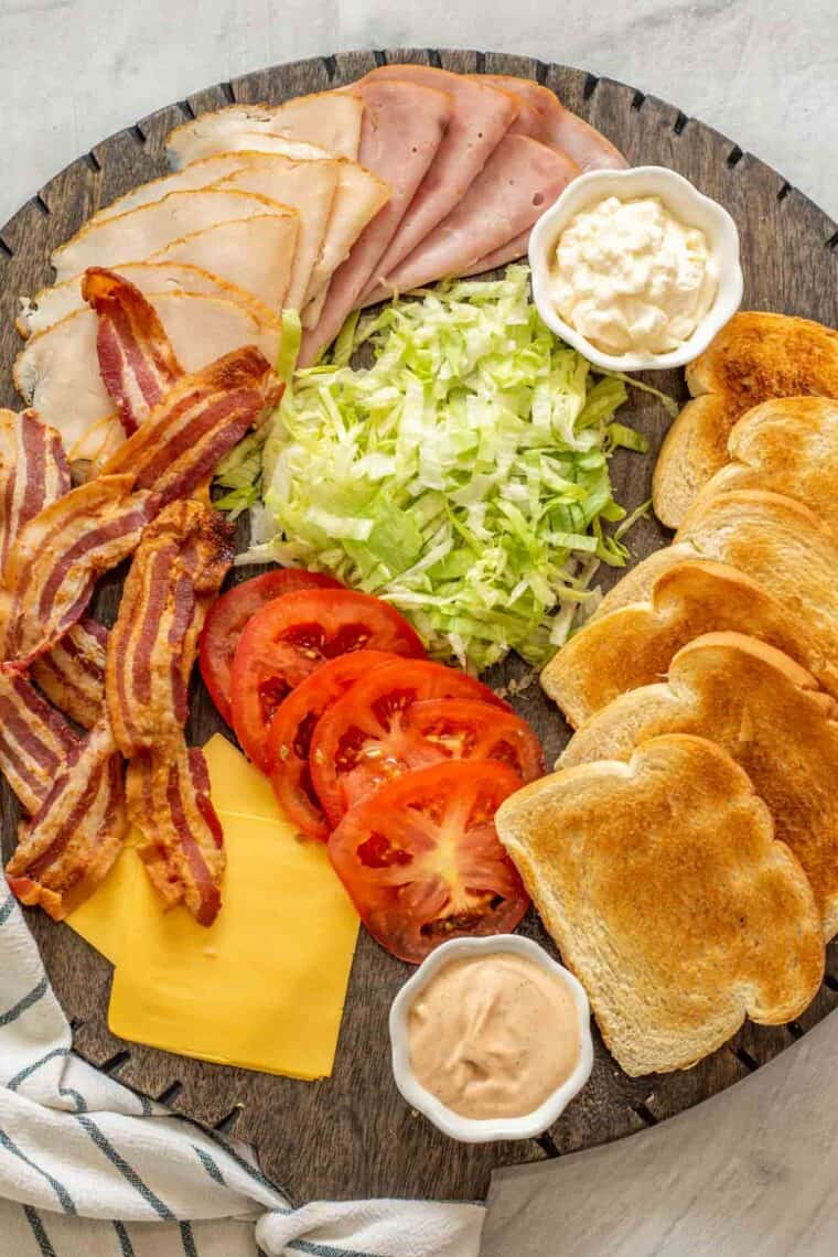All the ingredients needed for a club sandwich on a black wooden tray.
