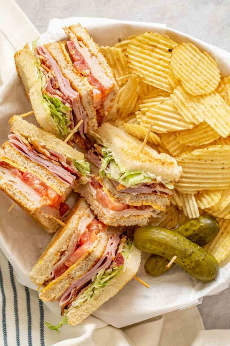 Club sandwich slices in a plate with chips.