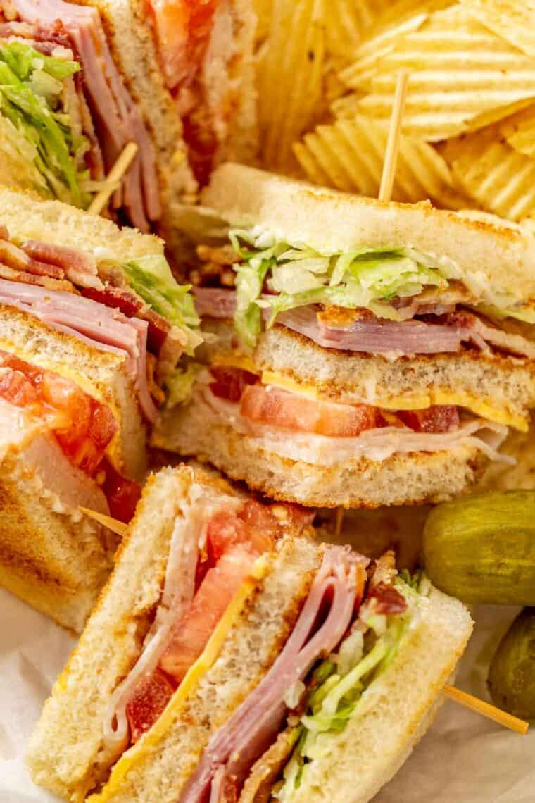 Club sandwich slices in a plate next to pickles and chips.