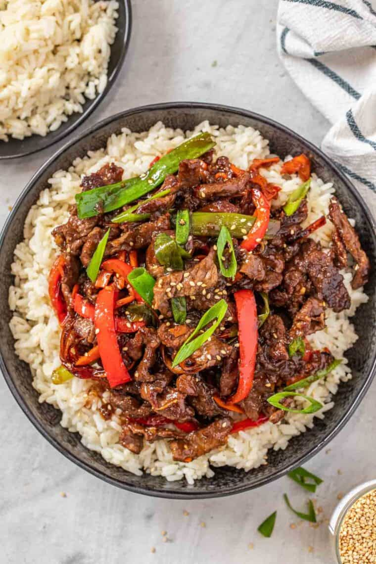 Ground beef stir fry over white rice in a black bowl topped with chopped greens and sesame seeds.